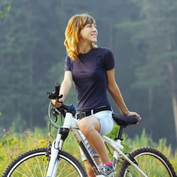 Use It Anywhere – Young woman on a bike in a forest