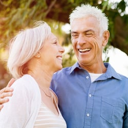 Total Well-being – Middle-aged couple laughing together under a tree