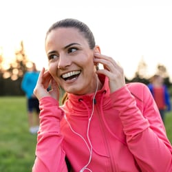 Think Clearer – Young woman outdoors with earbuds in ears and smiling