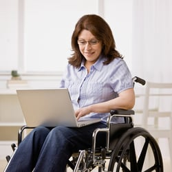 Stimulate Cognitive Function – Middle-aged woman in wheelchair on her laptop in the kitchen
