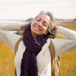 Age Gracefully – Middle-aged woman cheerfully stretching with her arms behind her head in a field