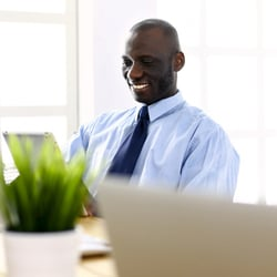 Encourages a Healthy Stress Response – Man sitting at desk happily working on his laptop