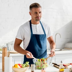 Supports Gut Health - Man tossing a bowl of salad in a white kitchen