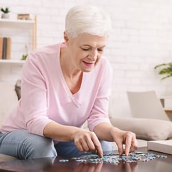 Stimulates Brain Function – Older woman working on a puzzle on a coffee table
