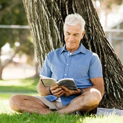 Supports a Focused Mind – Man sitting in grass under a tree reading a book