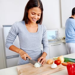Encourages a Balanced Mood – Woman chopping onions in a white kitchen