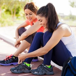 Prescription-Free Formula – Two female friends sitting on curb tying shoelaces in preparation to workout