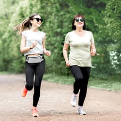 Helps You Adapt to Stress – Two females jogging on a park trail