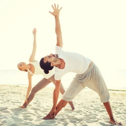 Soothes & Tones – Man and woman practicing yoga in the sand on the beach