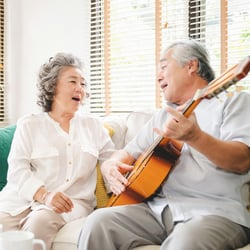 Enhanced Formula – Elderly Asian couple sitting on couch singing while paying the guitar