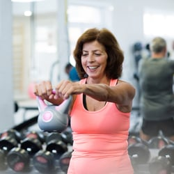 Stay Strong While Aging – Middle-aged woman using a kettlebell at the gym