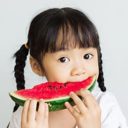 Gentle on the Stomach – Young Asian girl eating a slice of watermelon