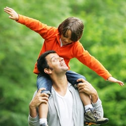 Encourages Parental Peace of Mind – Father carrying his son on his shoulders outdoors