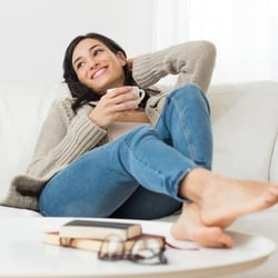 Support the Immune System – Young woman lounging on the couch with feet up on the coffee table and enjoying a cup of tea