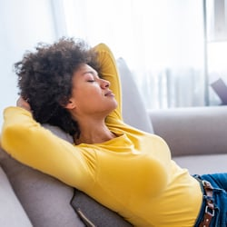 Promotes Joint Mobility - Woman with eyes closed leaning back on couch with her hands behind her head