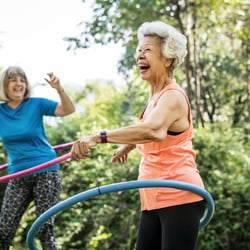 Gentle – Two middle-aged woman joyfully hula-hooping outdoors