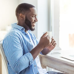 Easy on the Stomach – Man sitting in front of desk facing window and enjoying a cup of tea