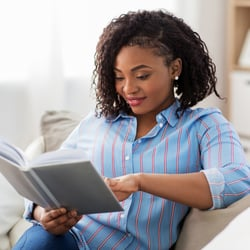 Promotes Brain Health  – Young woman resting on couch reading a book