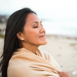 Supports the Immune System – Woman with eyes closed on the beach enjoying the breeze