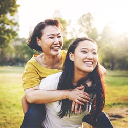 Supports Mental Well-Being – Young woman carrying her mom on her back in the park