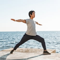 Restores Balance - Man doing standing yoga pose on cement block near the beach