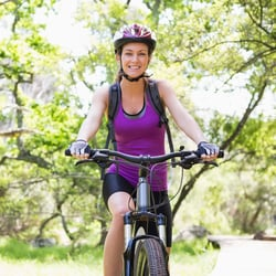 Elevates Total Health – Woman riding a bike on a park trail