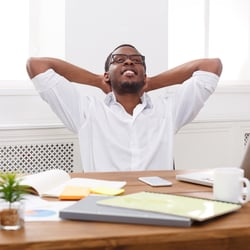Healthy Response to Stress – Man leaning back from desk with hands behind his head