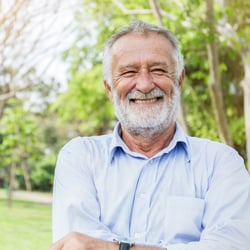 Encourages a Healthy Outlook – Older man standing in the park smiling