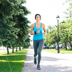 More Energy & Vitality – Young woman jogging on brick trail at the park