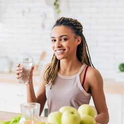 Feel Light & Healthy – Young woman drinking a glass of water in a white kitchen