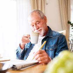 Sharper Brain Function – Middle-aged man working on a newspaper puzzle while drinking a cup of tea