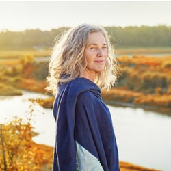 Stronger Gut – Middle-aged woman standing near lake and enjoying the autumn breeze