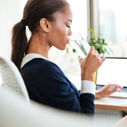 Enables Energy Levels – Woman drinking a glass of water at her desk
