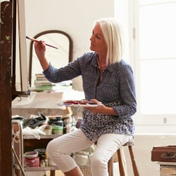 Supports Mental Agility – Middle-aged woman painting in a studio