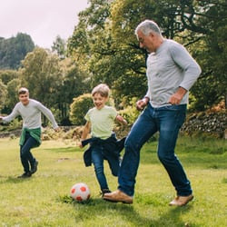 Facilitates Energy Production – Grandfather playing soccer with grandsons