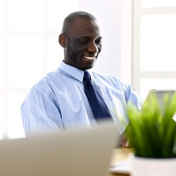 Optimizes Your Health – Young man in button-down shirt and tie sitting at desk on his tablet
