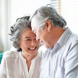 Lifts Your Spirits – Elderly Asian couple sitting close together and happily smiling at each other