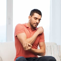 Soothes Bug Bites – Man sitting on couch holding onto one of his elbows