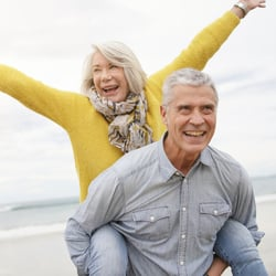 Slows Down Aging – Middle-aged man giving his wife a piggyback ride at the beach