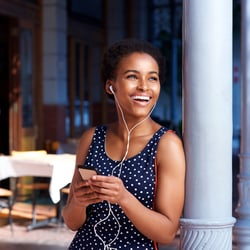 Bye-Bye Harmful Organisms – Woman smiling and listening to music while leaning against an outdoor pole