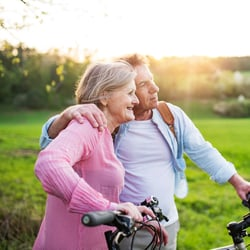 Seasonal Wellness – Middle-aged couple riding bicycles in the park