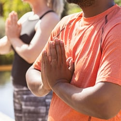 Encourages Healthy Nails – Man and woman practicing yoga with hands in prayer position