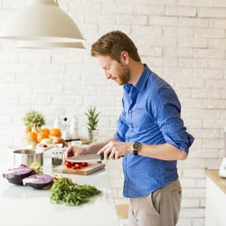Stomach Issues – Man chopping vegetables on a cutting board in a white kitchen