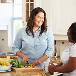 Better Nutrient Absorption – Two female friends gathered in kitchen laughing and cutting vegetables