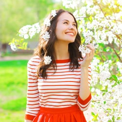 All-Natural Formula — Young woman smelling flowers outdoors