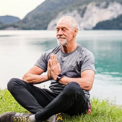 Senior bearded man in yoga meditation pose sitting over green grass by lake and mountains.