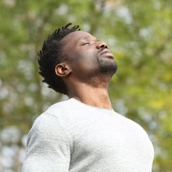 A man with eyes closed and head slightly tilted back taking a deep breath with the sun shining on his face.