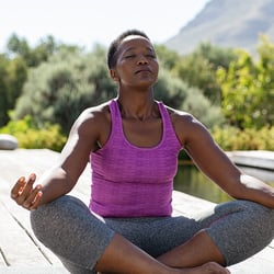 A woman in lotus meditation position sitting on a dock by a lake.