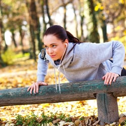 A woman in sportswear and listening to music with earphones while doing push-ups over a wooden ledge in a park.