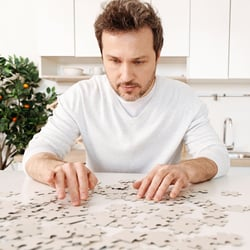 Promotes Brain Function – Man putting together a jigsaw puzzle